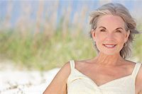 An attractive elegant senior woman sitting on a white sand beach with grass and a blue sky behind her. Stock Photo - Royalty-Freenull, Code: 400-04266202
