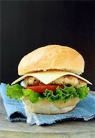 Cheeseburger with cheese and tomatoes on a stylish denim napkins Stock Photo - Royalty-Freenull, Code: 400-04300779