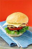 Cheeseburger with cheese and tomatoes on a stylish denim napkins Stock Photo - Royalty-Freenull, Code: 400-04304089
