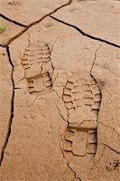 Boot footprints in dry cracked earth Stock Photo - Royalty-Freenull, Code: 400-04304444