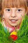 Little girl finds a multicoloured easter eggs in the tall green grass Stock Photo - Royalty-Free, Artist: fotostok_pdv                  , Code: 400-04313482