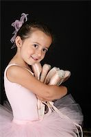 Cute brunette ballet girl holding lots of pointe shoes Stock Photo - Royalty-Freenull, Code: 400-04319401