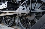 Closeup of vintage steem engine's black, iron wheel