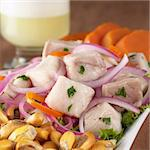 Peruvian-style ceviche made out of raw dogfish (Spanish: tollo), red onions and aji (Peruvian hot pepper) and served with roasted corn (cancha) and sweet potato with Pisco Sour (Peruvian traditional cocktail) in the back (Selective Focus, Focus on the front of the fish) Stock Photo - Royalty-Free, Artist: ildi                          , Code: 400-04334359