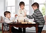 Three twin brothers playing chess game in room Stock Photo - Royalty-Free, Artist: fotostok_pdv                  , Code: 400-04344792
