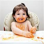 Happy baby having fun eating messy covered in Spaghetti Angel Hair Pasta red marinara tomato sauce. Stock Photo - Royalty-Free, Artist: phakimata                     , Code: 400-04345317