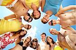 Below view of circle of friends looking at camera with blue sky above them Stock Photo - Royalty-Free, Artist: pressmaster                   , Code: 400-04356903