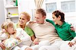 A young family of four sitting on sofa and looking at cute girl Stock Photo - Royalty-Free, Artist: pressmaster                   , Code: 400-04357577