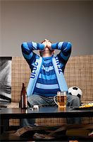 fat man balls - soccer fan is sitting on sofa with beer at home Stock Photo - Royalty-Freenull, Code: 400-04358882