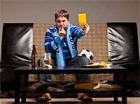fat man balls - soccer fan is sitting on sofa with beer and showing yellow card at home Stock Photo - Royalty-Freenull, Code: 400-04358883