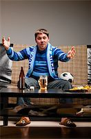 fat man balls - soccer fan is sitting on sofa with beer at home and applauding Stock Photo - Royalty-Freenull, Code: 400-04358884