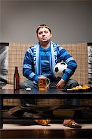 fat man balls - soccer fan is sitting on sofa with beer at home Stock Photo - Royalty-Freenull, Code: 400-04358885