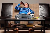 fat man balls - soccer fan is sitting on sofa with beer at home Stock Photo - Royalty-Freenull, Code: 400-04358888
