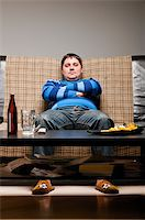 fat man balls - soccer fan is sitting on sofa with beer at home Stock Photo - Royalty-Freenull, Code: 400-04358890