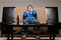 soccer fan is sitting on sofa with beer at home Stock Photo - Royalty-Freenull, Code: 400-04358891