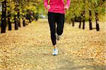 Image of female legs jogging among autumn trees