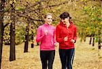 Two girls jogging in autumn park and smiling
