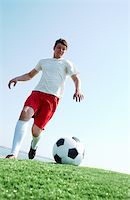 Portrait of a soccer player going to kick ball on football field Stock Photo - Royalty-Freenull, Code: 400-04361735