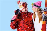 Portrait of happy couple with skis in hands looking at each other and smiling