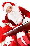 Portrait of Santa Claus looking at camera in front of laptop with gifts near by Stock Photo - Royalty-Free, Artist: pressmaster                   , Code: 400-04362962