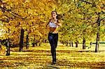 A young girl jogging among golden autumn trees