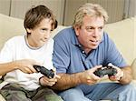 Uncle and nephew (or father and son) playing video games together. Stock Photo - Royalty-Free, Artist: lisafx                        , Code: 400-04364302