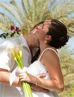 A young newly married couple sharing a romantic kiss Stock Photo - Royalty-Freenull, Code: 400-04367586