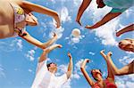 Below view of teenage friends catching ball on background of cloudy sky Stock Photo - Royalty-Free, Artist: pressmaster                   , Code: 400-04371788