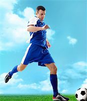 Portrait of a soccer player with ball on a blue background Stock Photo - Royalty-Freenull, Code: 400-04373299