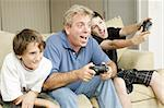 Uncle and his two nephews playing video games together.  Could also be father and sons. Stock Photo - Royalty-Free, Artist: lisafx                        , Code: 400-04374237