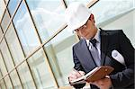 Portrait of confident foreman in helmet writing business plan Stock Photo - Royalty-Free, Artist: pressmaster                   , Code: 400-04383580