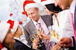 Image of cheering friends in Santa caps making toast at corporate party Stock Photo - Royalty-Free, Artist: pressmaster                   , Code: 400-04386322