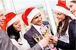 Image of cheering friends in Santa caps making toast at corporate party Stock Photo - Royalty-Free, Artist: pressmaster                   , Code: 400-04386336