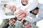 Below shot of smiling co-workers making pile of hands and looking at camera Stock Photo - Royalty-Free, Artist: pressmaster                   , Code: 400-04386582