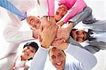 Below shot of smiling co-workers making pile of hands and looking at camera Stock Photo - Royalty-Free, Artist: pressmaster                   , Code: 400-04388317