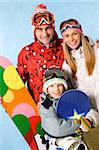 Portrait of happy family with snowboards looking at camera on blue background Stock Photo - Royalty-Free, Artist: pressmaster, Code: 400-04388818