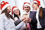 Image of cheering friends in Santa caps making toast at corporate party Stock Photo - Royalty-Free, Artist: pressmaster                   , Code: 400-04388926