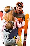 Portrait of happy family with snowboards and skis looking at each other and chatting