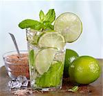 glass of mojito cocktail, fresh limes and brown sugar