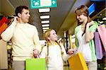 Image of family carrying bags and interacting in the mall Stock Photo - Royalty-Free, Artist: pressmaster                   , Code: 400-04395474
