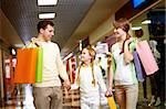 Image of family carrying bags and interacting in the mall Stock Photo - Royalty-Free, Artist: pressmaster                   , Code: 400-04395475