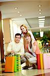 Image of family with paperbags looking at camera in the mall Stock Photo - Royalty-Free, Artist: pressmaster                   , Code: 400-04395479
