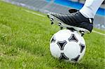 Horizontal image of soccer ball in green grass with foot of player touching it Stock Photo - Royalty-Free, Artist: pressmaster                   , Code: 400-04396257
