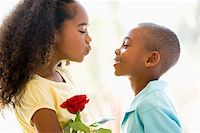 people kissing little boys - Young boy giving young girl rose and smiling Stock Photo - Royalty-Freenull, Code: 400-04401521