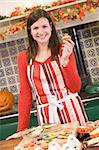 Woman in kitchen making Halloween treats and smiling Stock Photo - Royalty-Free, Artist: MonkeyBusinessImages          , Code: 400-04402167