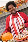Woman in kitchen making Halloween treats and smiling Stock Photo - Royalty-Free, Artist: MonkeyBusinessImages          , Code: 400-04402187