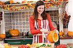 Woman carving jack o lantern on Halloween and smiling Stock Photo - Royalty-Free, Artist: MonkeyBusinessImages          , Code: 400-04402191