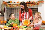 Mother and two children carving jack o lanterns on Halloween and Stock Photo - Royalty-Free, Artist: MonkeyBusinessImages          , Code: 400-04402192