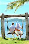 Rear view bride and groom on the swing