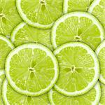 Abstract green background with citrus-fruit of lime slices. Close-up. Studio photography. Stock Photo - Royalty-Free, Artist: boroda                        , Code: 400-04423839